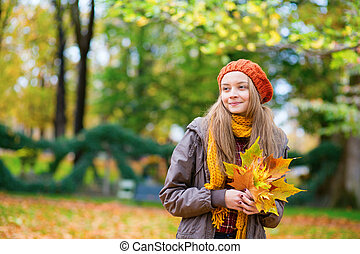 Cheerful young girl with bunch of leaves