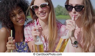 Cheerful young girls having beer