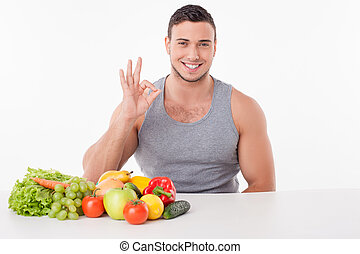 Cheerful young guy is eating healthy food and gesturing