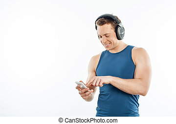 Cheerful young guy is relaxing and selcting songs