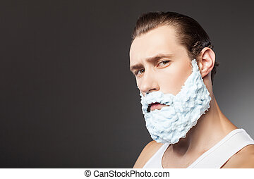 Cheerful young guy is shaving his beard