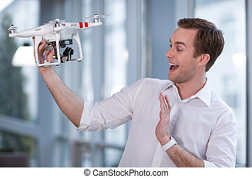 Cheerful young guy is using a drone