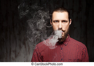 Cheerful young guy with beard is smoking