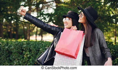 Cheerful young ladies shopaholics are taking selfie in the...