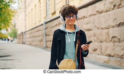 Cheerful young lady is listening to music through headphones...