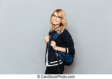 Cheerful young lady student with backpack