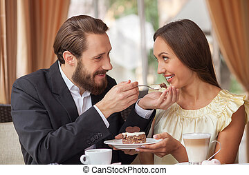 Cheerful young loving couple is dating in restaurant