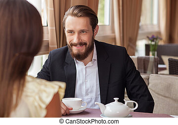 Cheerful young loving couple is meeting in cafe