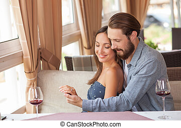 Cheerful young loving couple is resting in restaurant