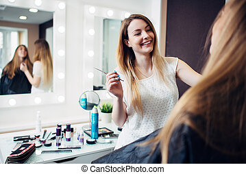 Cheerful young makeup artist working with a customer holding...