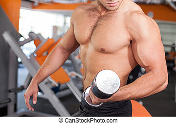 Cheerful young male sportsman is training in fitness center