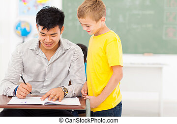 young male teacher grading school boy's work