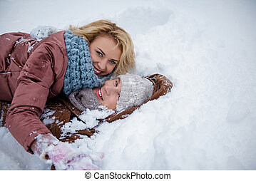 Cheerful young man and woman are having fun on snow