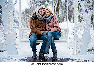 Cheerful young man and woman cuddling in cold weather