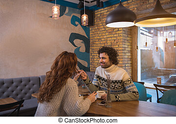 Cheerful young man and woman dating in restaurant