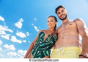 Cheerful young man and woman enjoying their vacation on beach