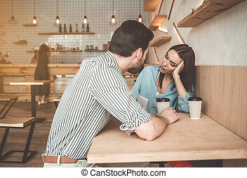 Cheerful young man and woman flirting in cafeteria