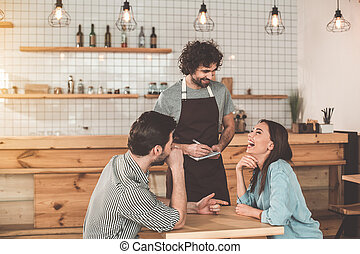 Cheerful young man and woman making order in cafe