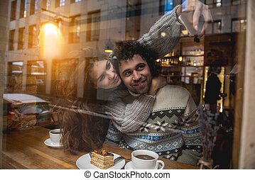 Cheerful young man and woman taking photos on cellphone