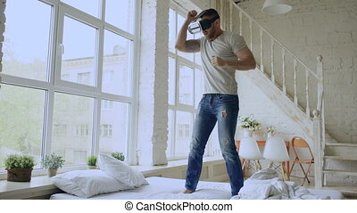Cheerful young man dancing while getting experience using 360 VR headset glasses of virtual reality on bed at home