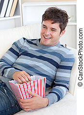 Cheerful young man eating popcorn lying on the sofa