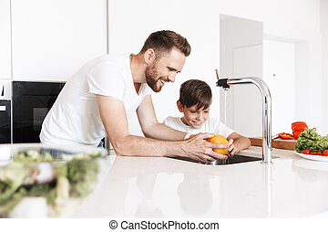 Cheerful young man father dad cooking with his son