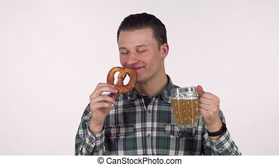 Cheerful young man holding mug of beer, smelling delicious pretzel