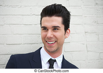 Cheerful young man in business suit smiling outdoors