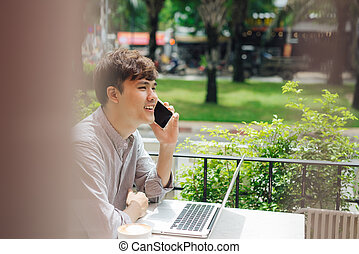 Cheerful young man in casual wear talking on the mobile phone while sitting in cafe.
