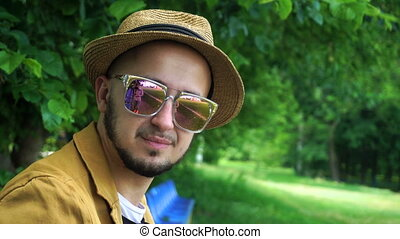 Cheerful young man in hat and sunglasses smiling on camera