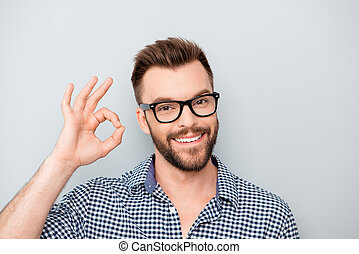 """Cheerful young man in spectacles showing """"OK"""" gesture"""