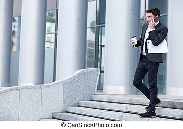 Cheerful young man in suit is using telephone
