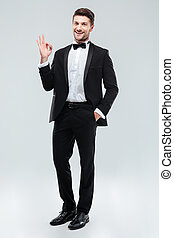 Cheerful young man in tuxedo with bowtie showing ok sign