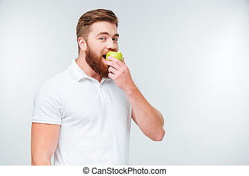 Cheerful young man is eating apple