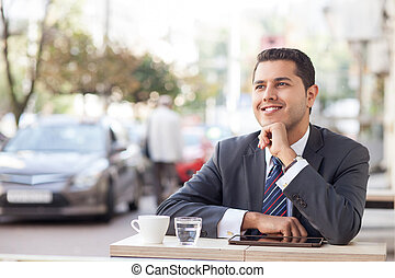 Cheerful young man is resting in cafeteria