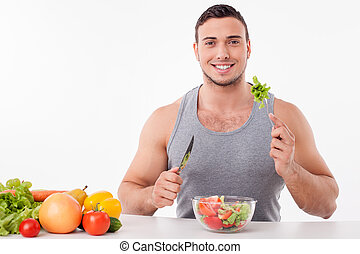 Cheerful young man is tasting healthy food