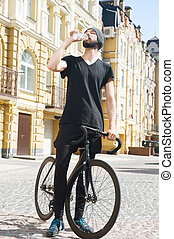 Cheerful young man is thirsty after cycling