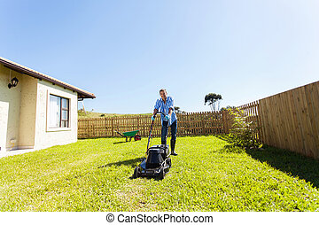 cheerful young man mowing lawn at home