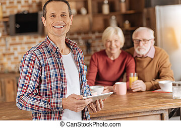 Cheerful young man posing with tablet in the kitchen