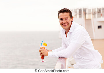 young man relaxing on cruise deck with cocktail - cheerful...