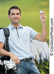 cheerful young man showing golf ball while standing on field