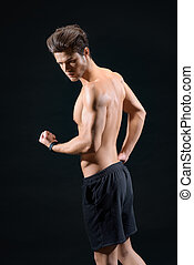 Cheerful young man showing his bicep