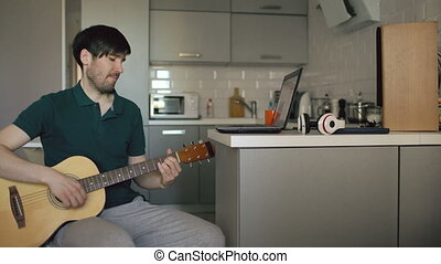 Cheerful young man sitting at kitchen learning to play guitar using laptop computer at home