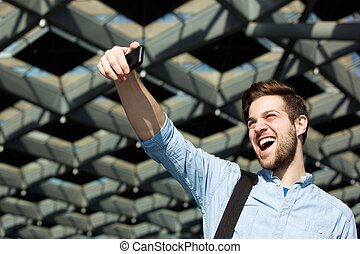 Cheerful young man taking selfie