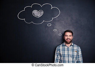 Cheerful young man thinking about love over background of chalkboard