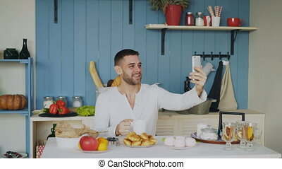 Cheerful young man using smartphone for online video chat...