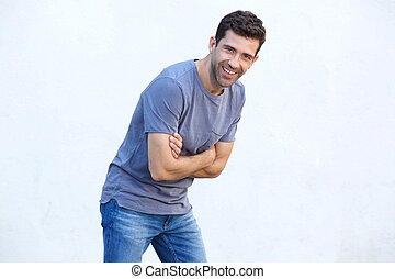 Cheerful young man with arms crossed standing against white wall