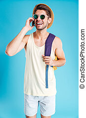 Cheerful young man with backpack talking on cell phone