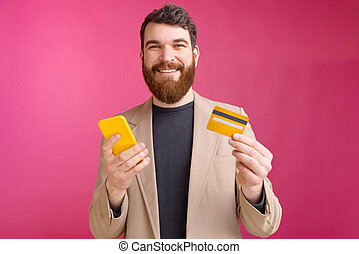 Cheerful young man with beard in suit using smartphone and credit card, mobile web banking