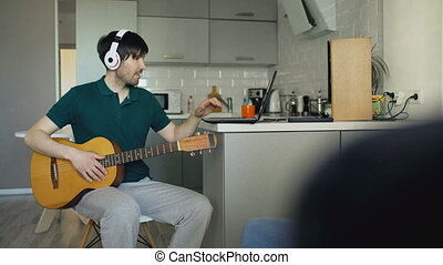 Cheerful young man with headphones sitting at kitchen...